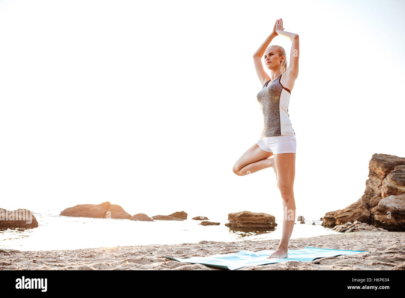 Portrait of a young woman standing in yoga pose on one leg on beach - Stock Image