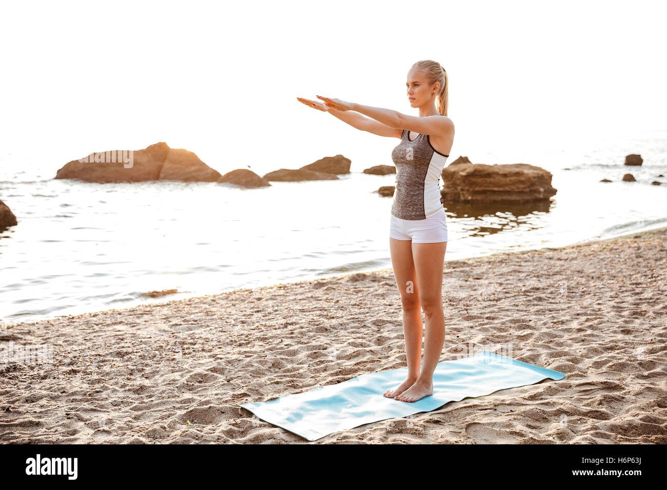 Beautiful young woman doing stretching exercises during yoga on the beach - Stock Image