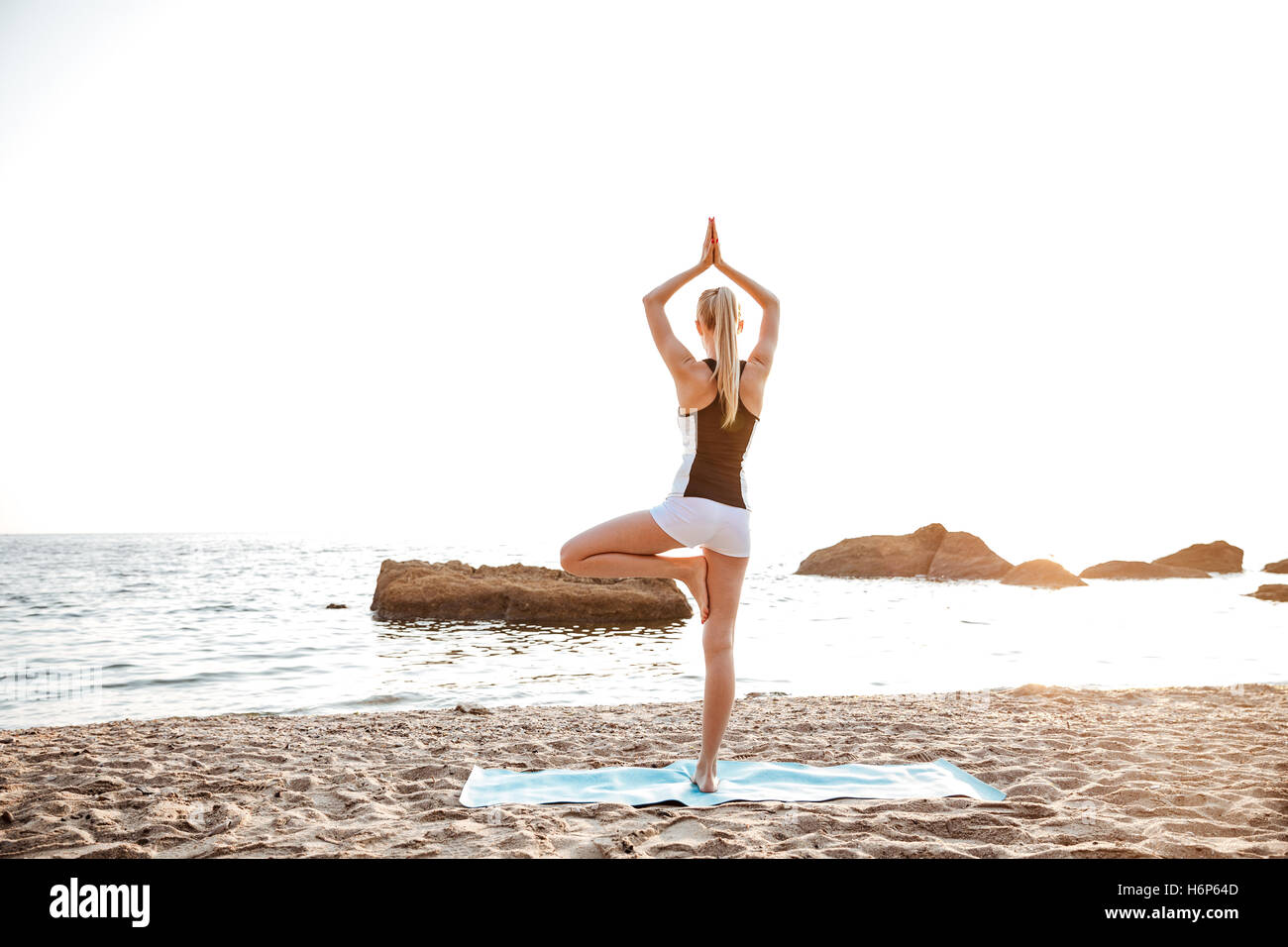 Back view of a young woman standing in yoga pose on one leg on beach - Stock Image