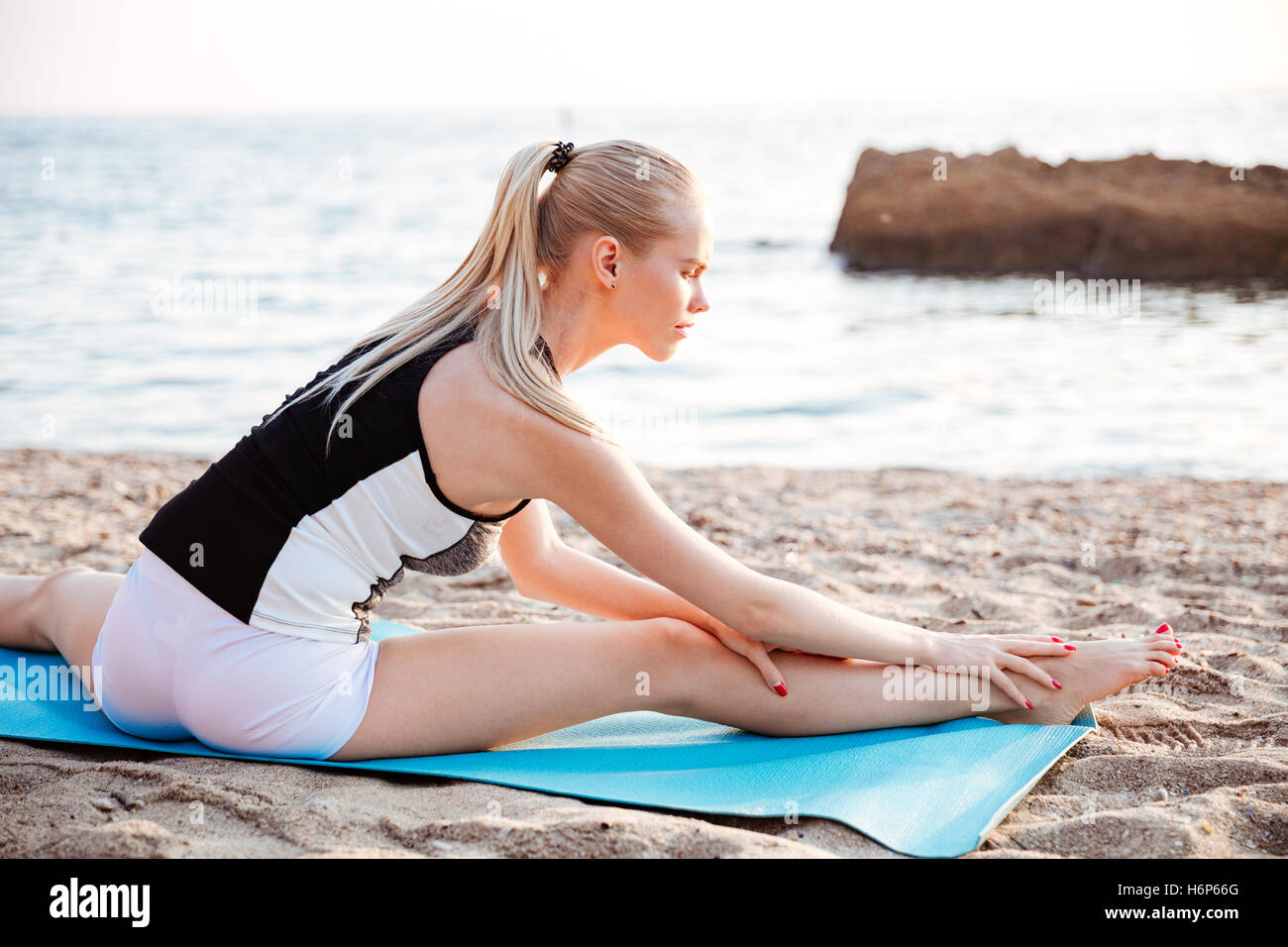 Portrait of a young blonde woman doing stretching exercises on yoga mat outdoors in the morning - Stock Image