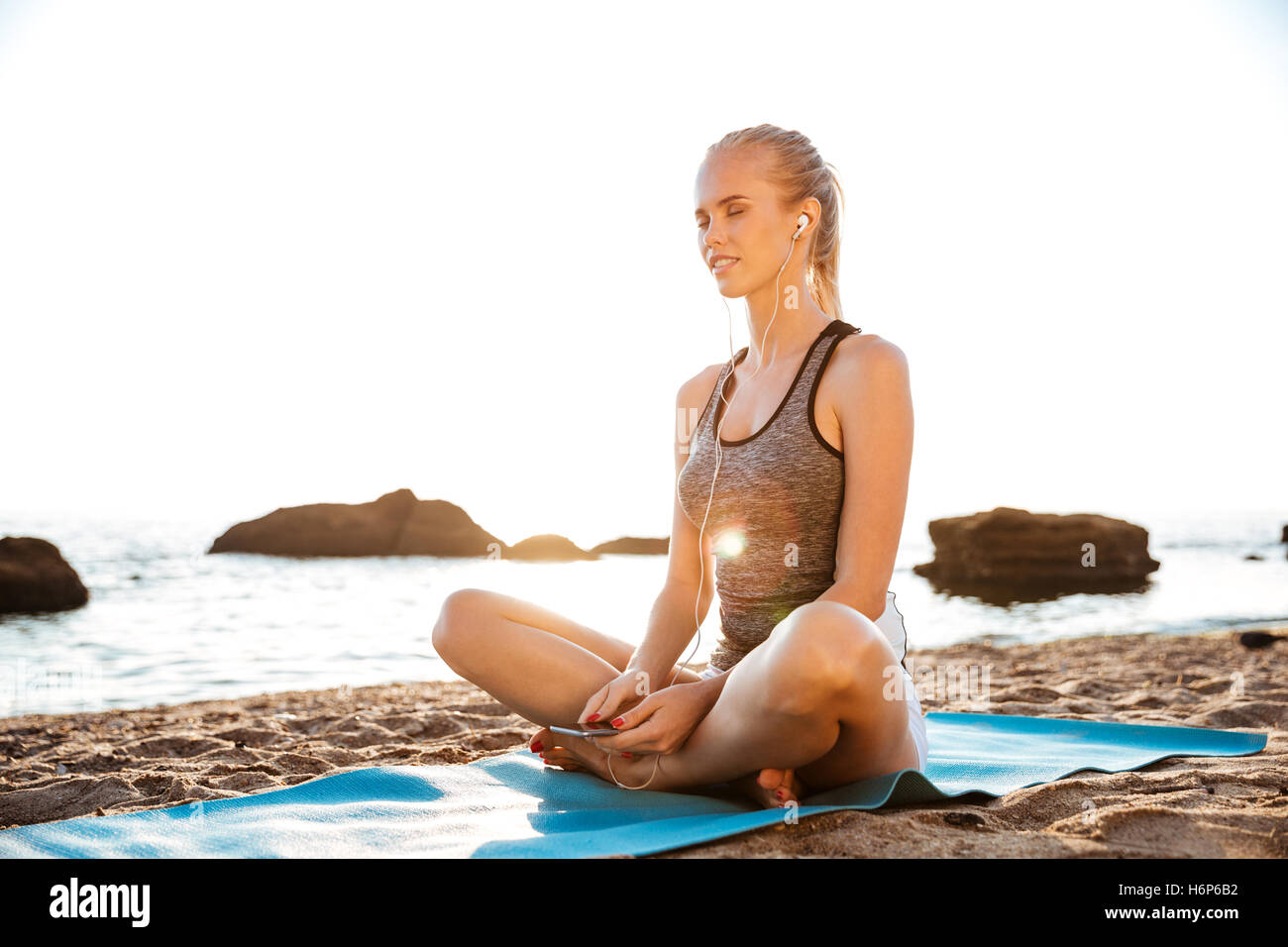 Beautiful young woman with eyes closed listening music on beach - Stock Image