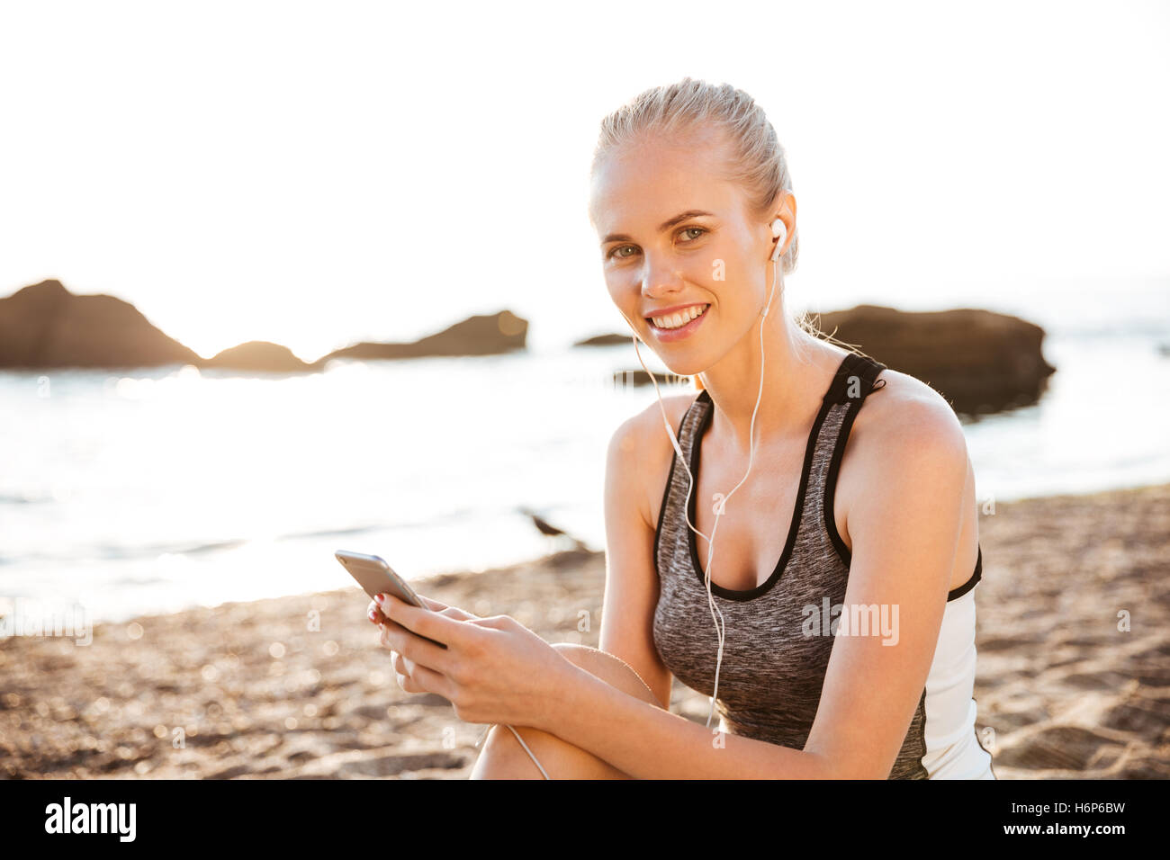 Close up portrait of a smiling blonde sports woman with earphones sitting on beach - Stock Image