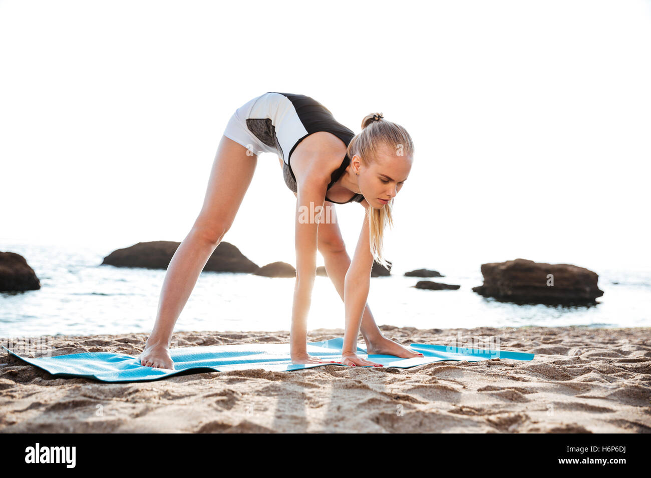 Peaceful young woman doing relaxing yoga exercises outdoors - Stock Image
