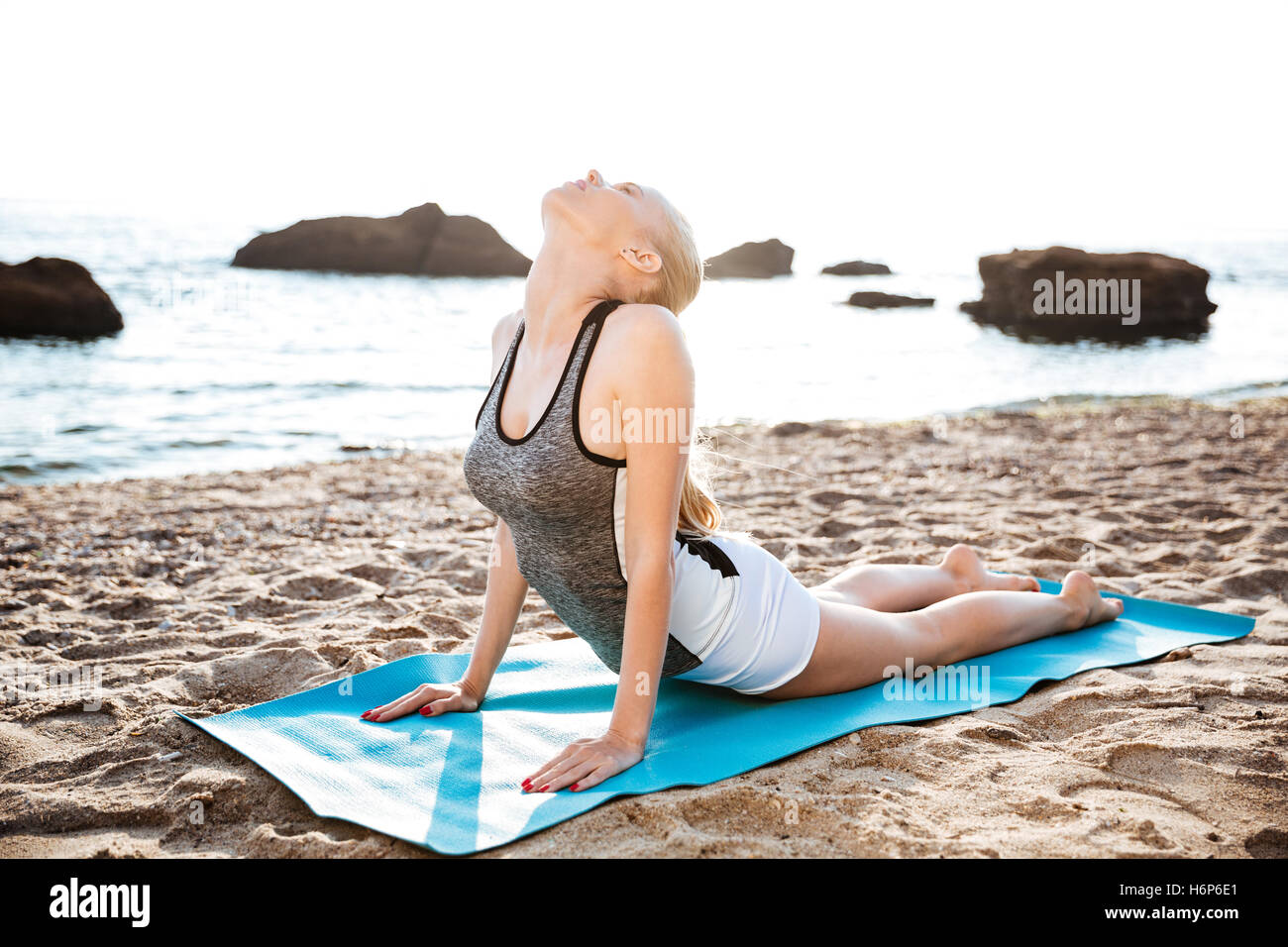 Flexible young woman doing stretching yoga exercises on beach - Stock Image