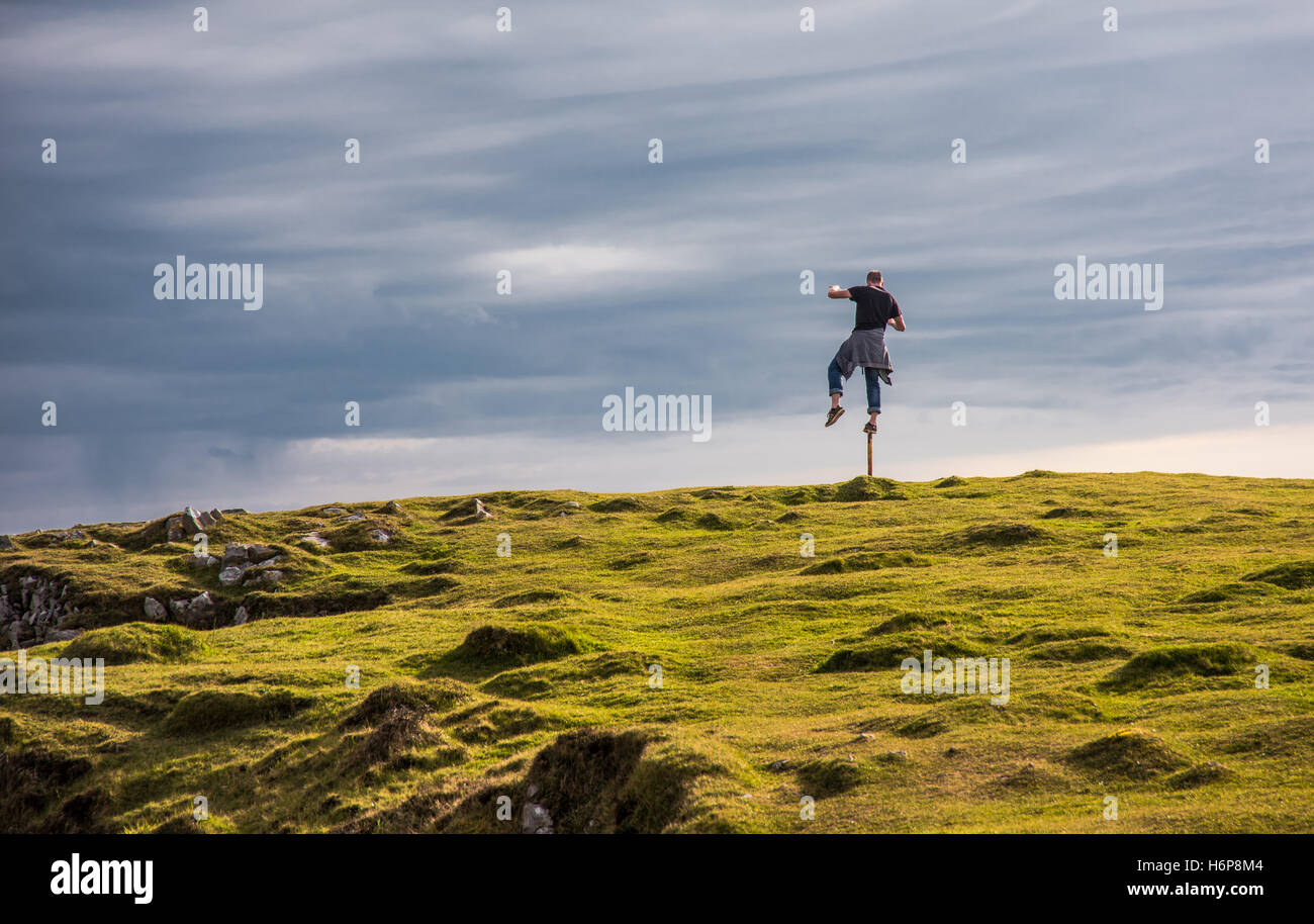 An energetic man takes a brief interlude from running to to test his balance on a stake. - Stock Image