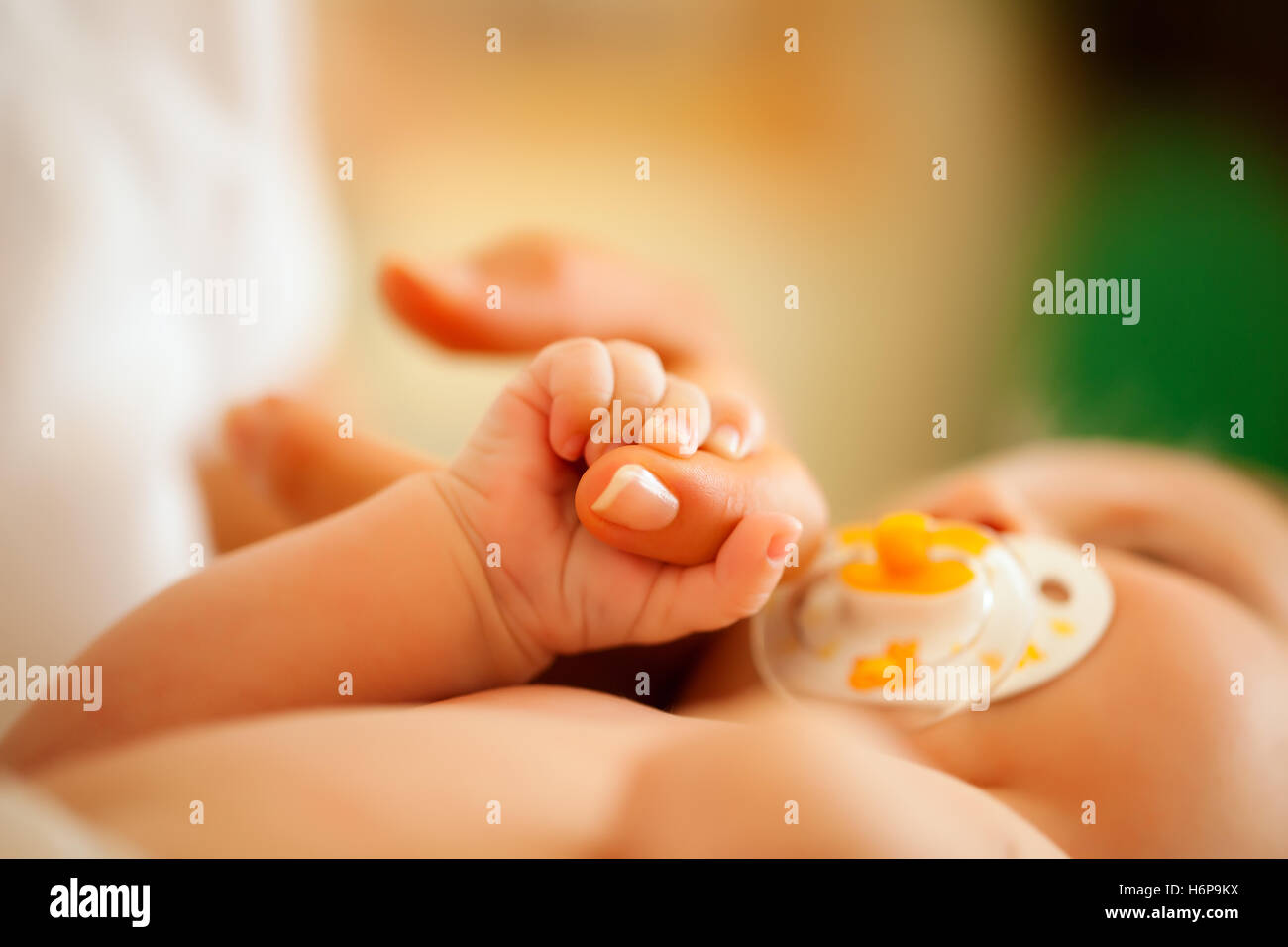 baby with mother reaches for hand - Stock Image