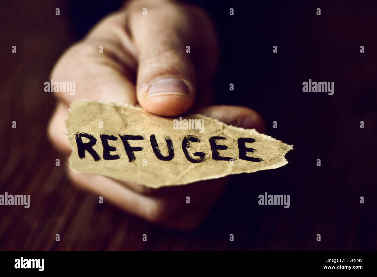 closeup of the hand of a young man with a piece of paper with the word refugee, with a dramatic effect - Stock Image