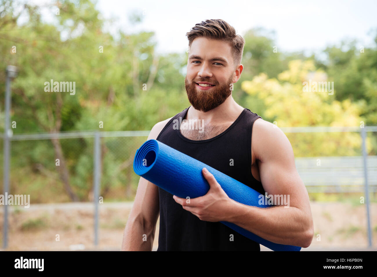 Handsome bearded young sportsman holding yoga mat and looking at camera outdoors - Stock Image