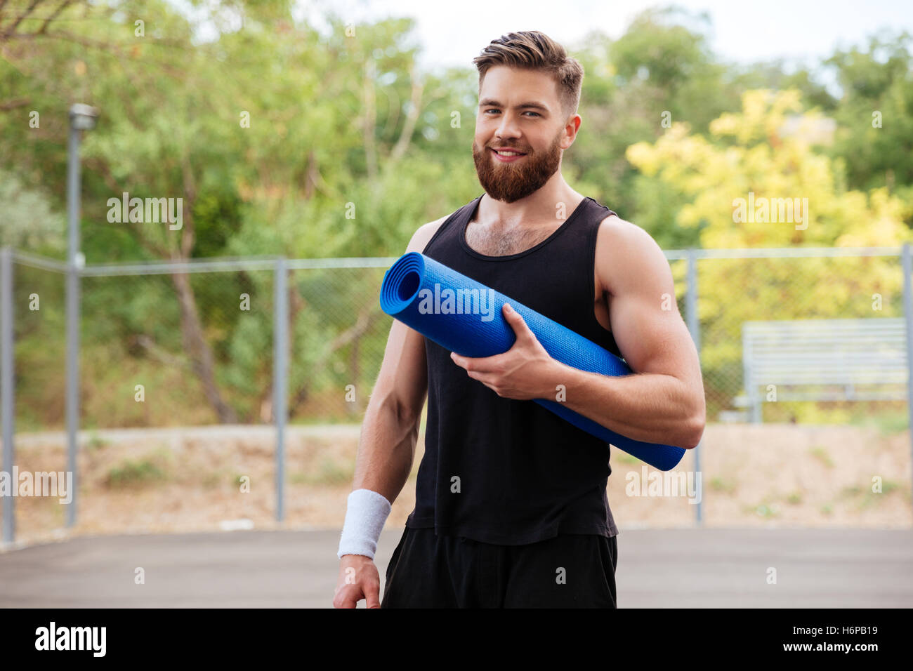 Smiling cheerful bearded fitness man with yoga mat standing outdoors - Stock Image