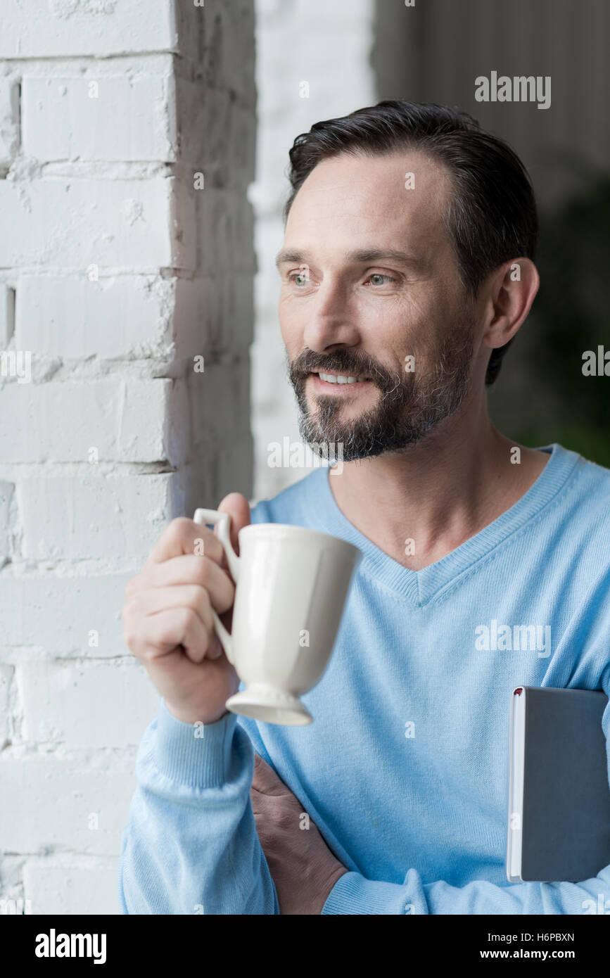 Nice bearded man enjoying his coffee - Stock Image