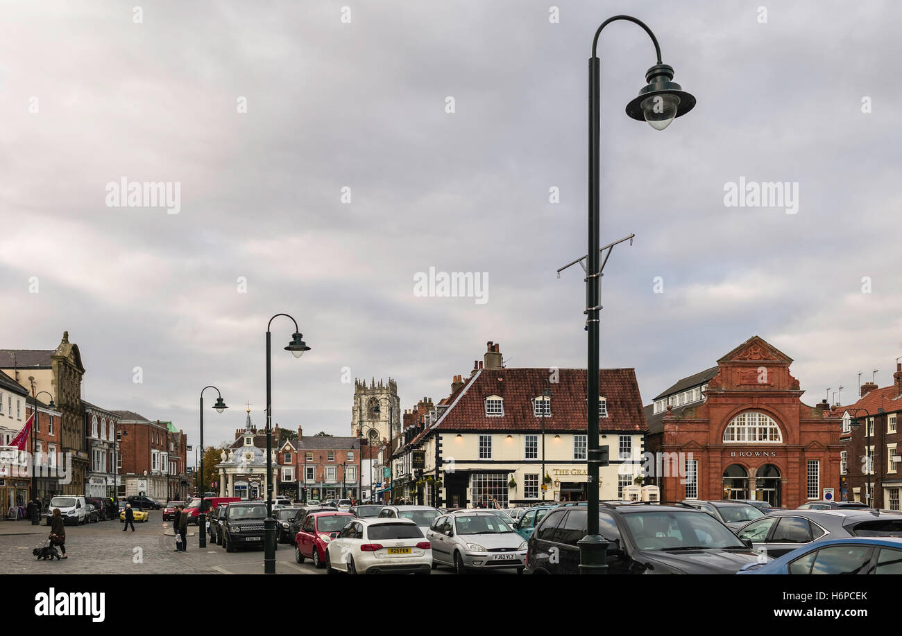 Town centre with view of shops, cars, public, and St Mary's church on an overcast day in autumn in Beverley, Yorkshire, Stock Photo