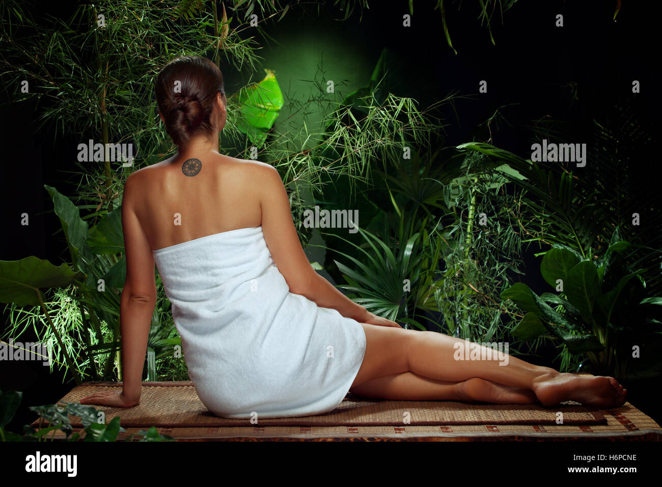 View of nice young woman meditating in spa tropic environment - Stock Image