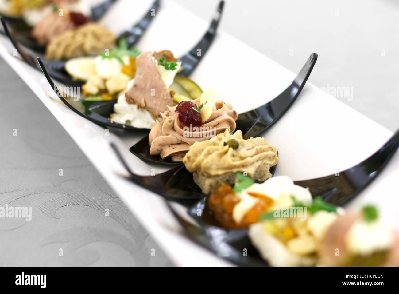 Canapes on black plastic spoons on ceramic tray. - Stock Image