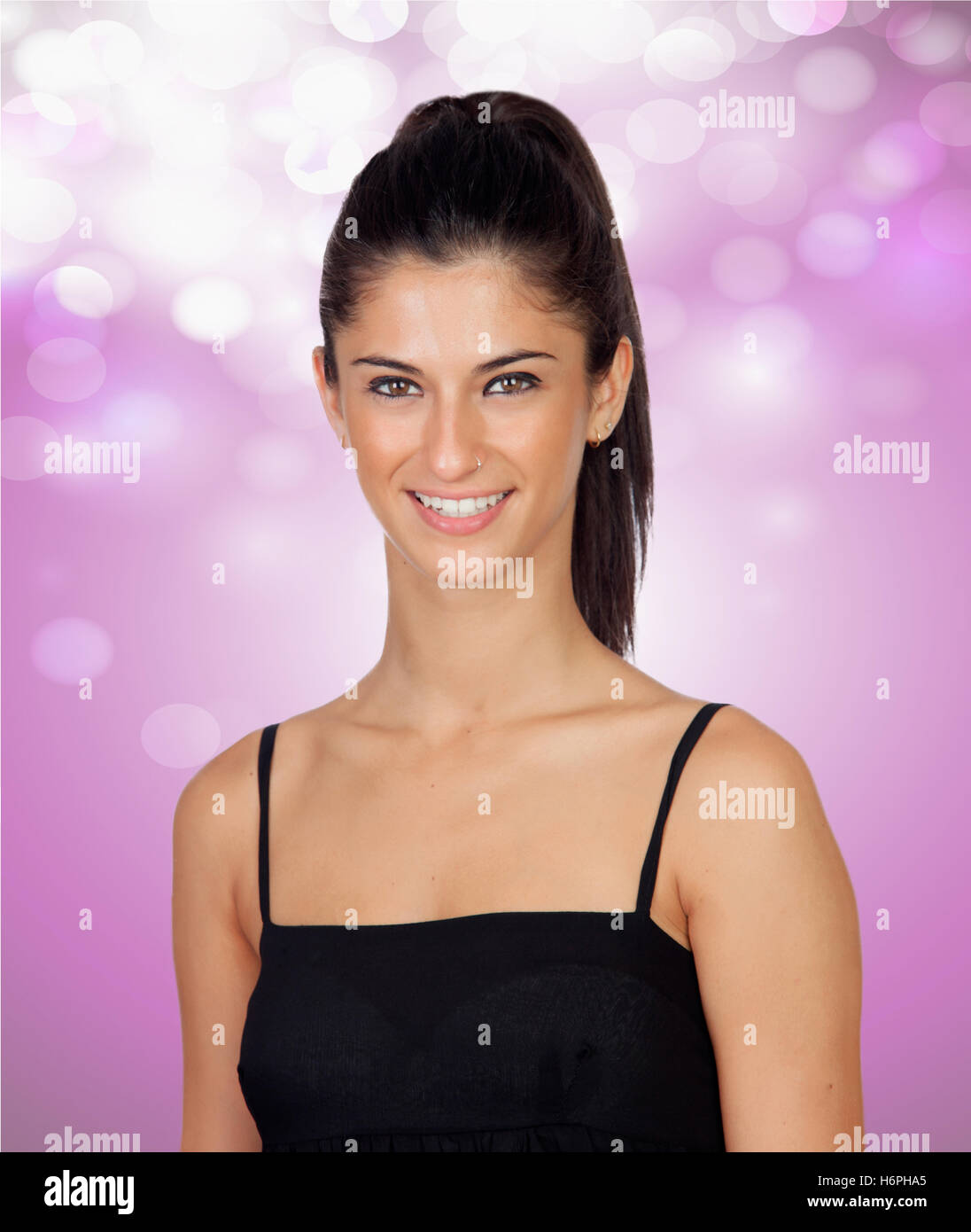 Attractive brunette girl with a pierced nose on a pink and bright background Stock Photo
