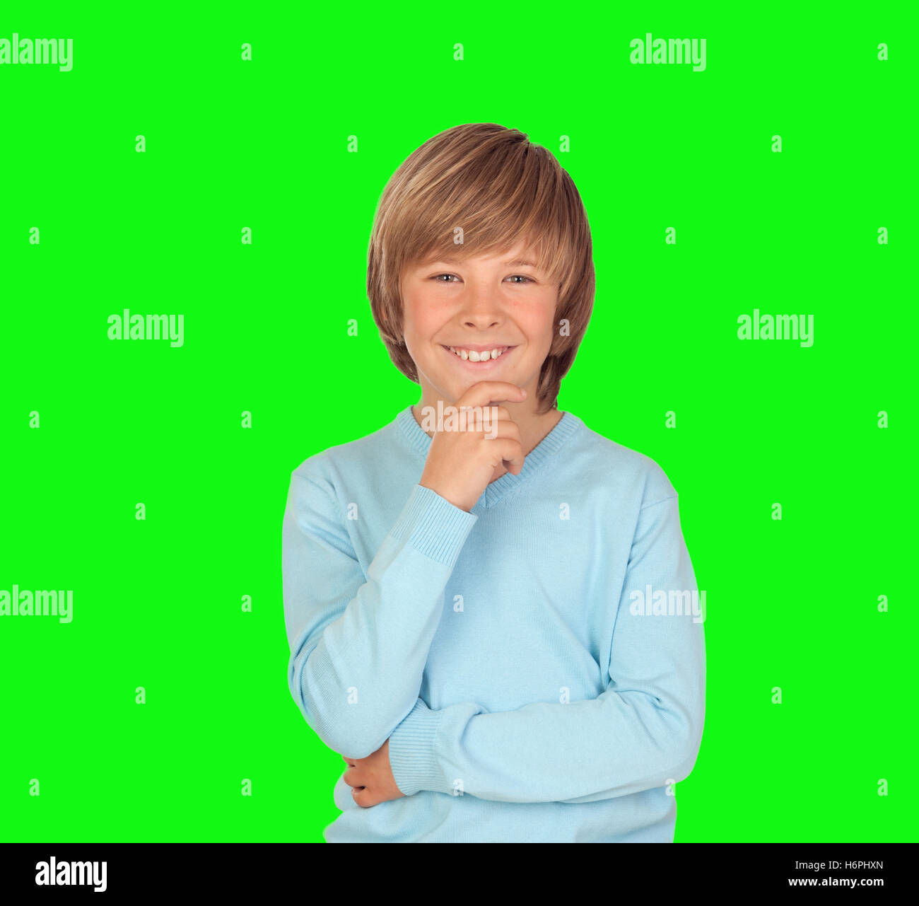 Pensive preteen boy isolated on a over green background - Stock Image