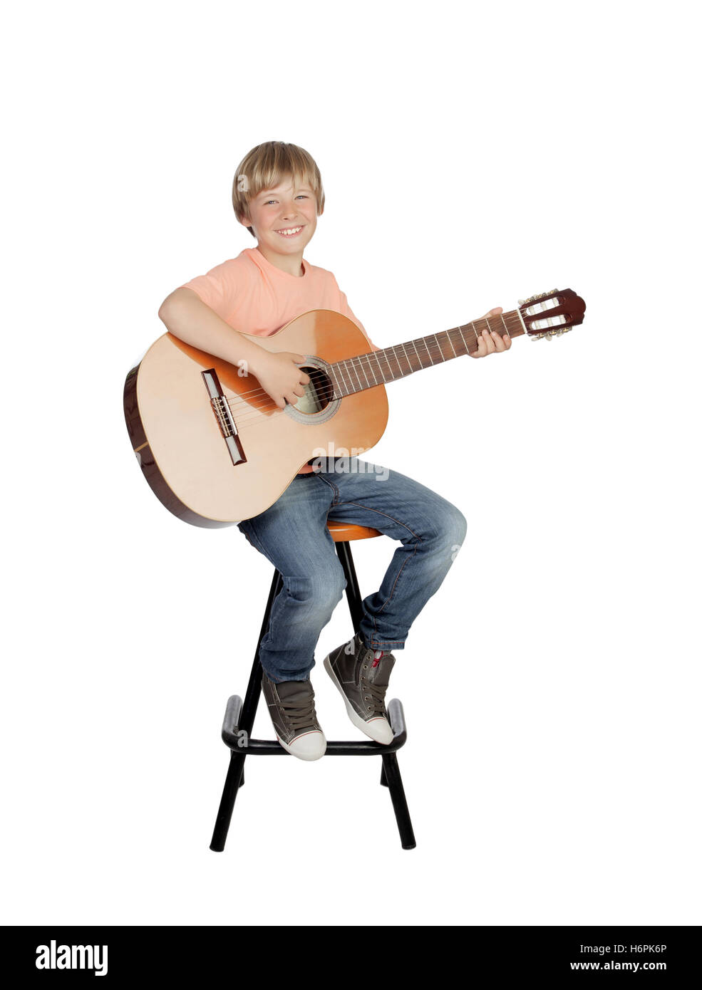 Smiling boy with a guitar isolated on white background - Stock Image