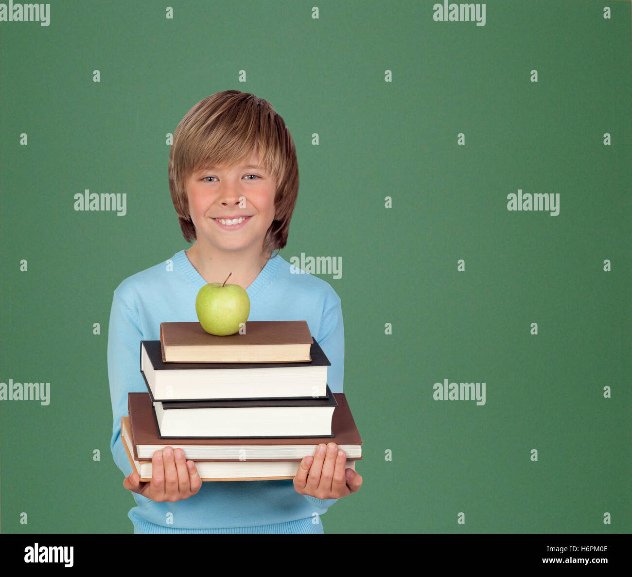 Preteen boy with a many books with a green blackboard for backgrond - Stock Image