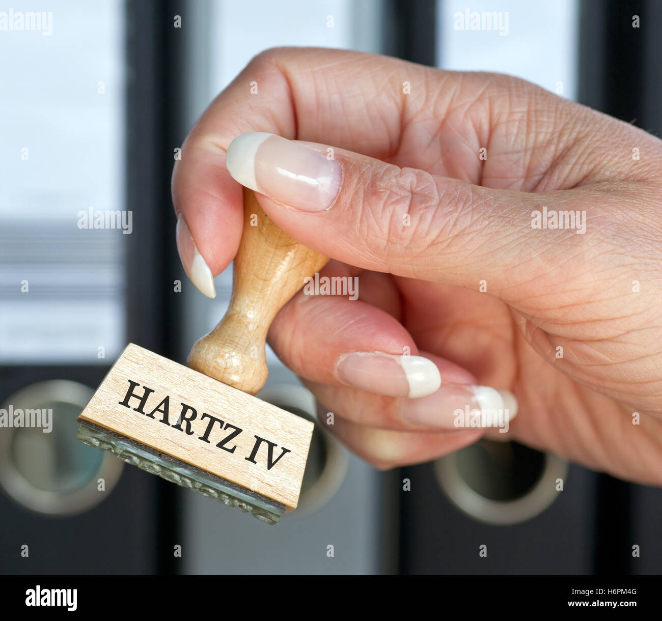 hartz iv - stamp labour office with hand - Stock Image