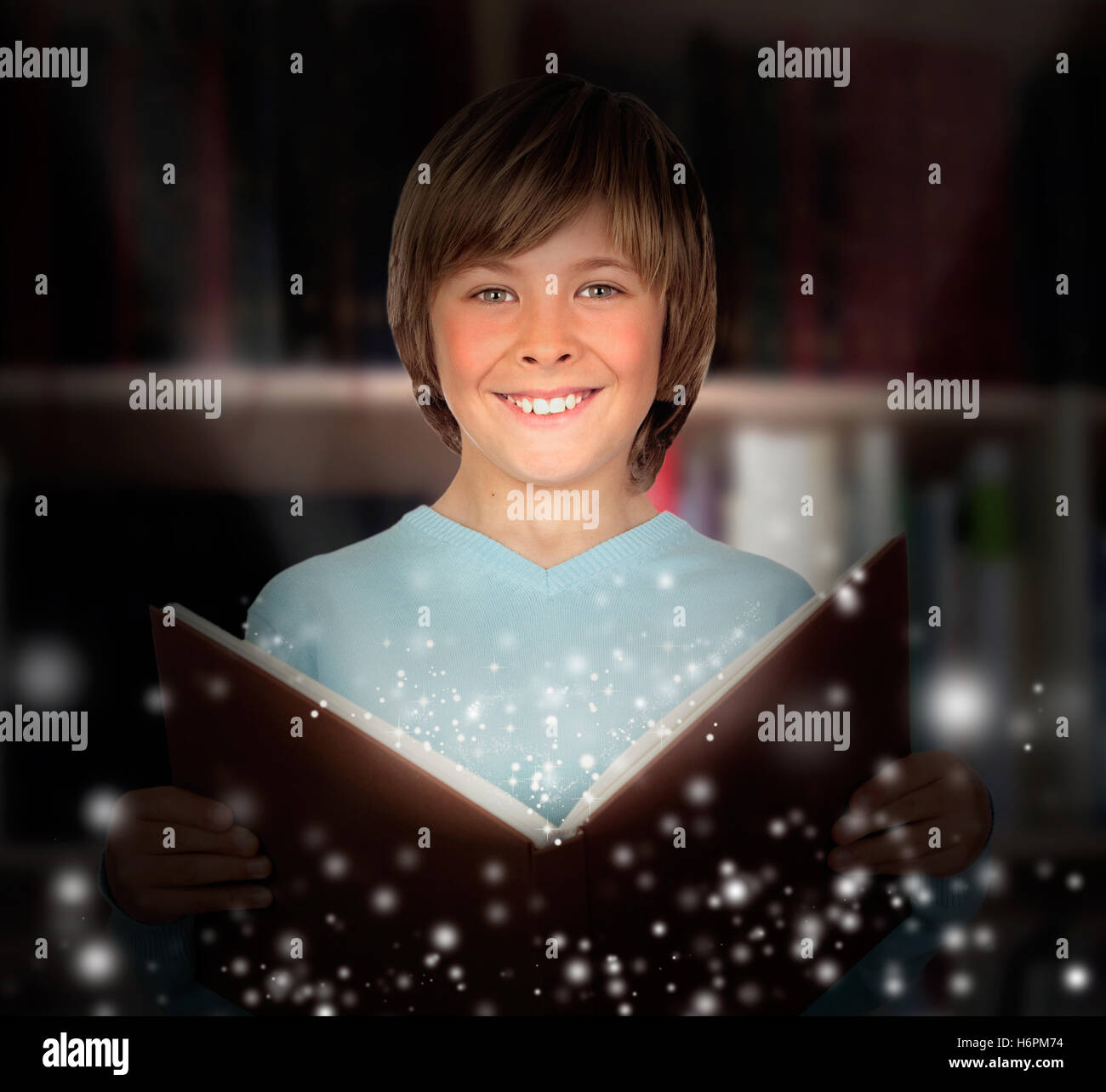 Preteen boy with a lighted book reading in the library - Stock Image