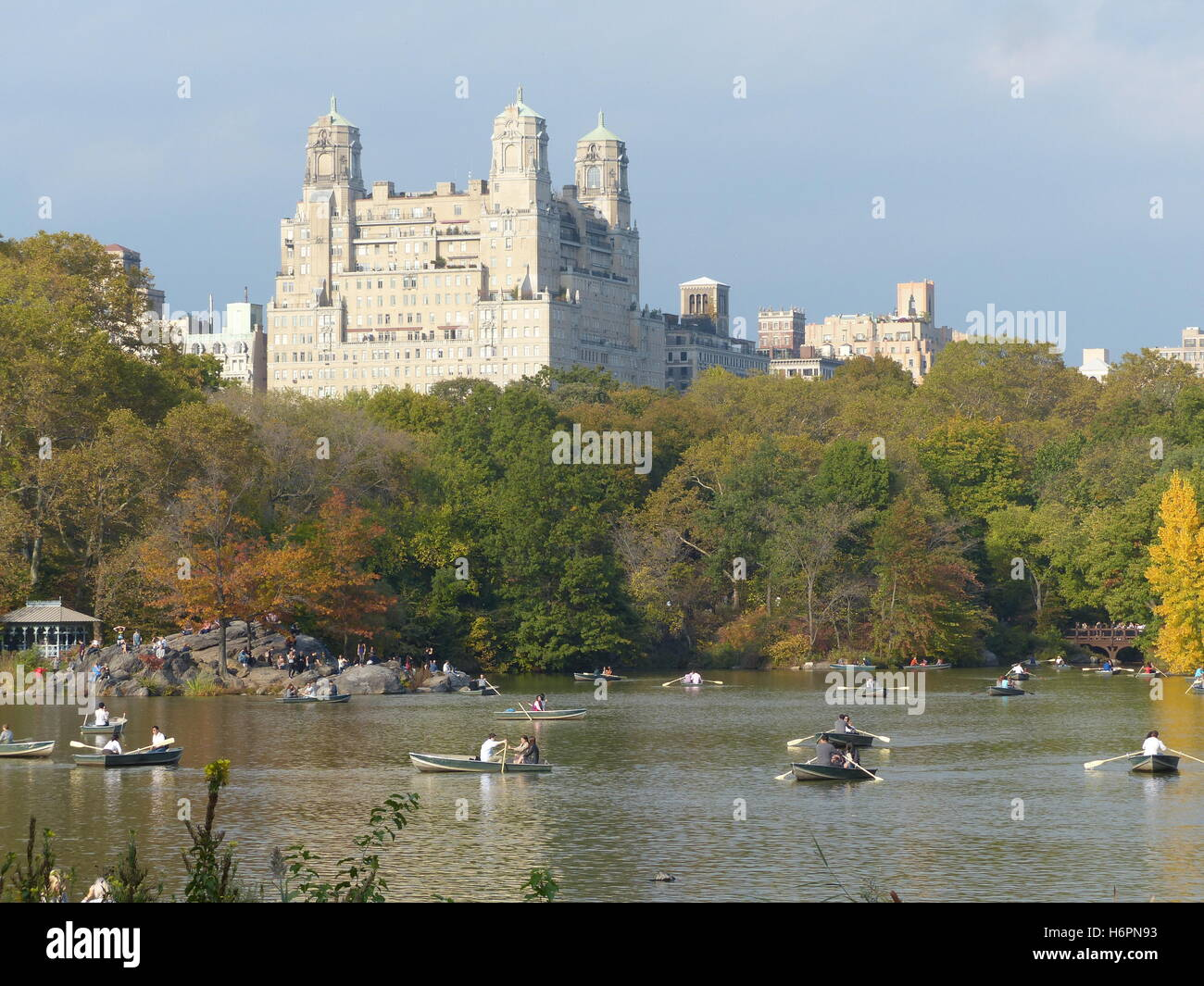 Row boats with couples in Central Park, NY with The Beresford residential tower designed by Architect Emery Roth, - Stock Image