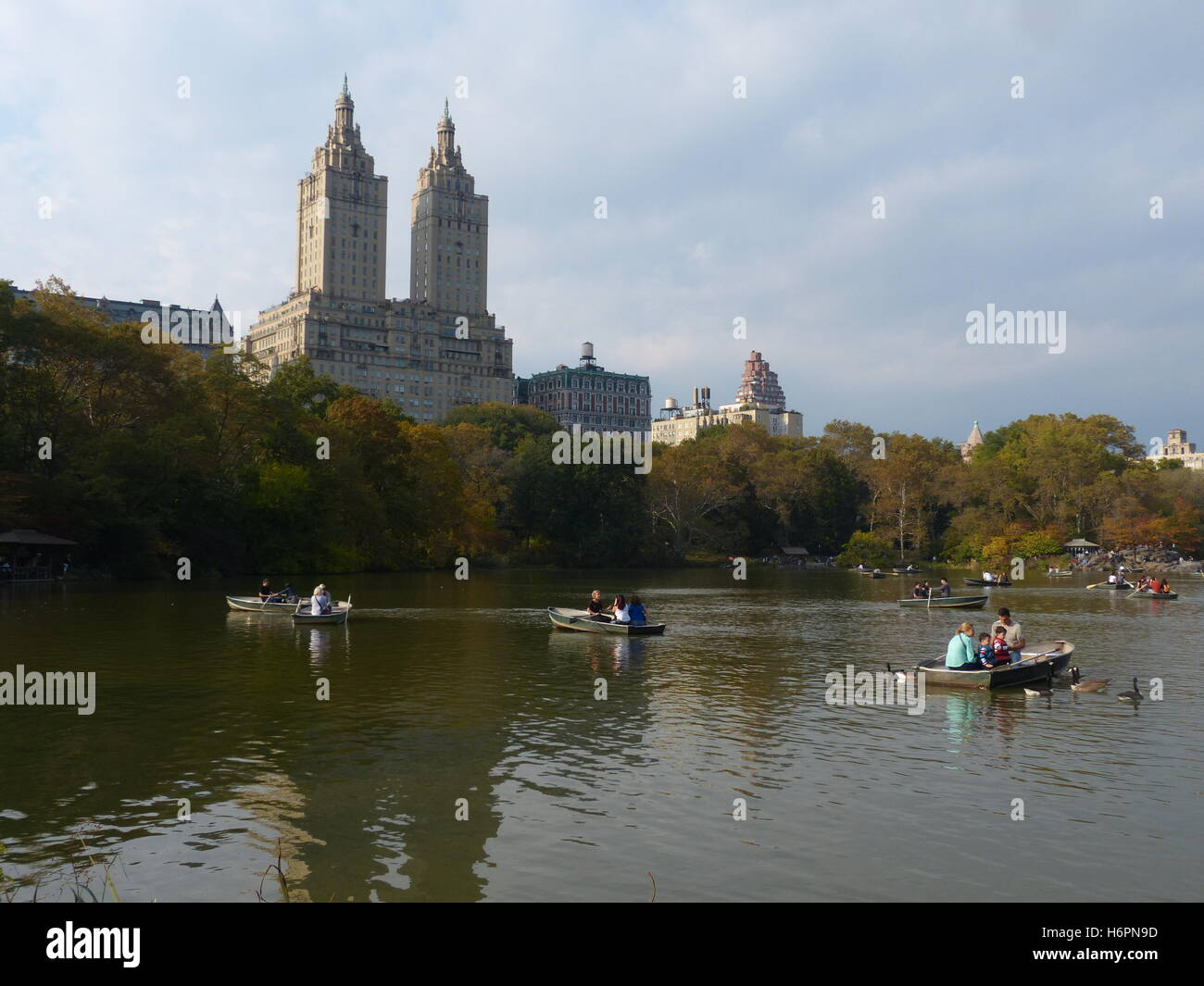Row boats with couples in Central Park, NY with San Remo residential towers in background designed by Architect - Stock Image