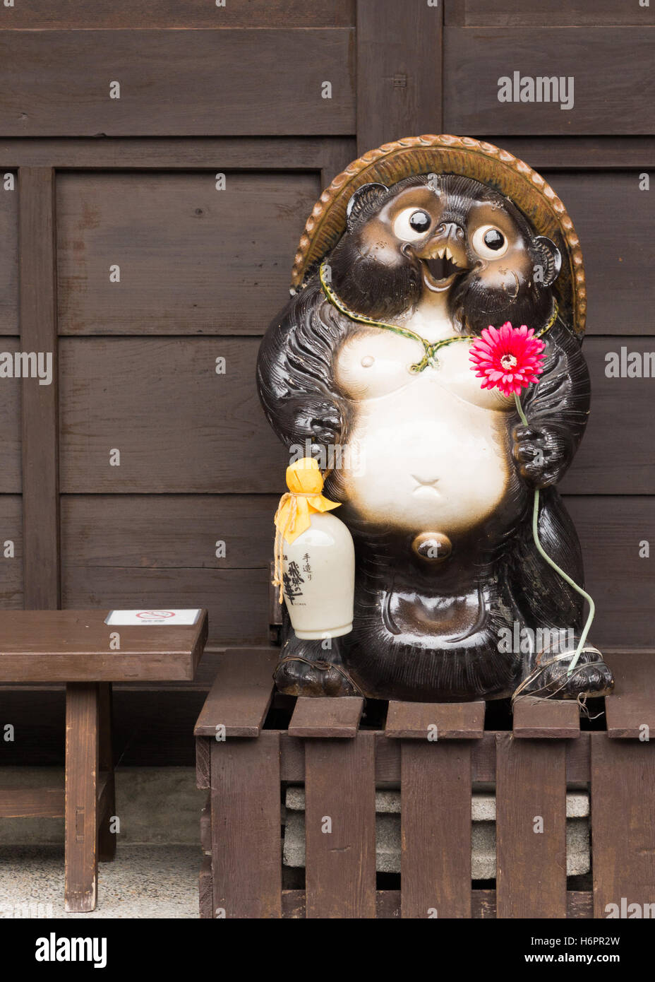 Tanuki statue holds red flower and the customary Sake flask. - Stock Image