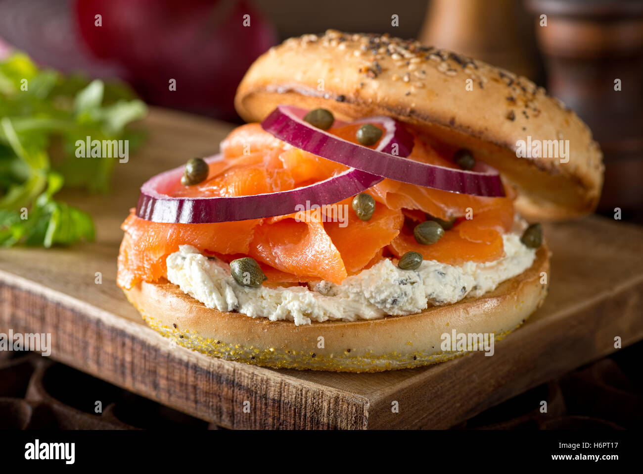 A delicious toasted bagel with smoked salmon, cream cheese, capers, and red onion. Stock Photo