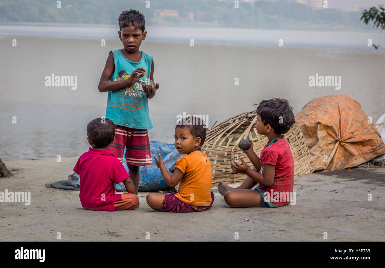 Street children play with clay from the Ganges river bank at Mallick Ghat, flower market, Kolkata, India. - Stock Image