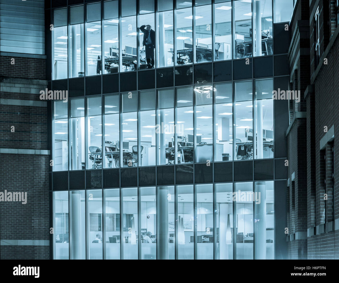 office glass windows. Man Looking Out Of Office Window At Night. Glass Windows