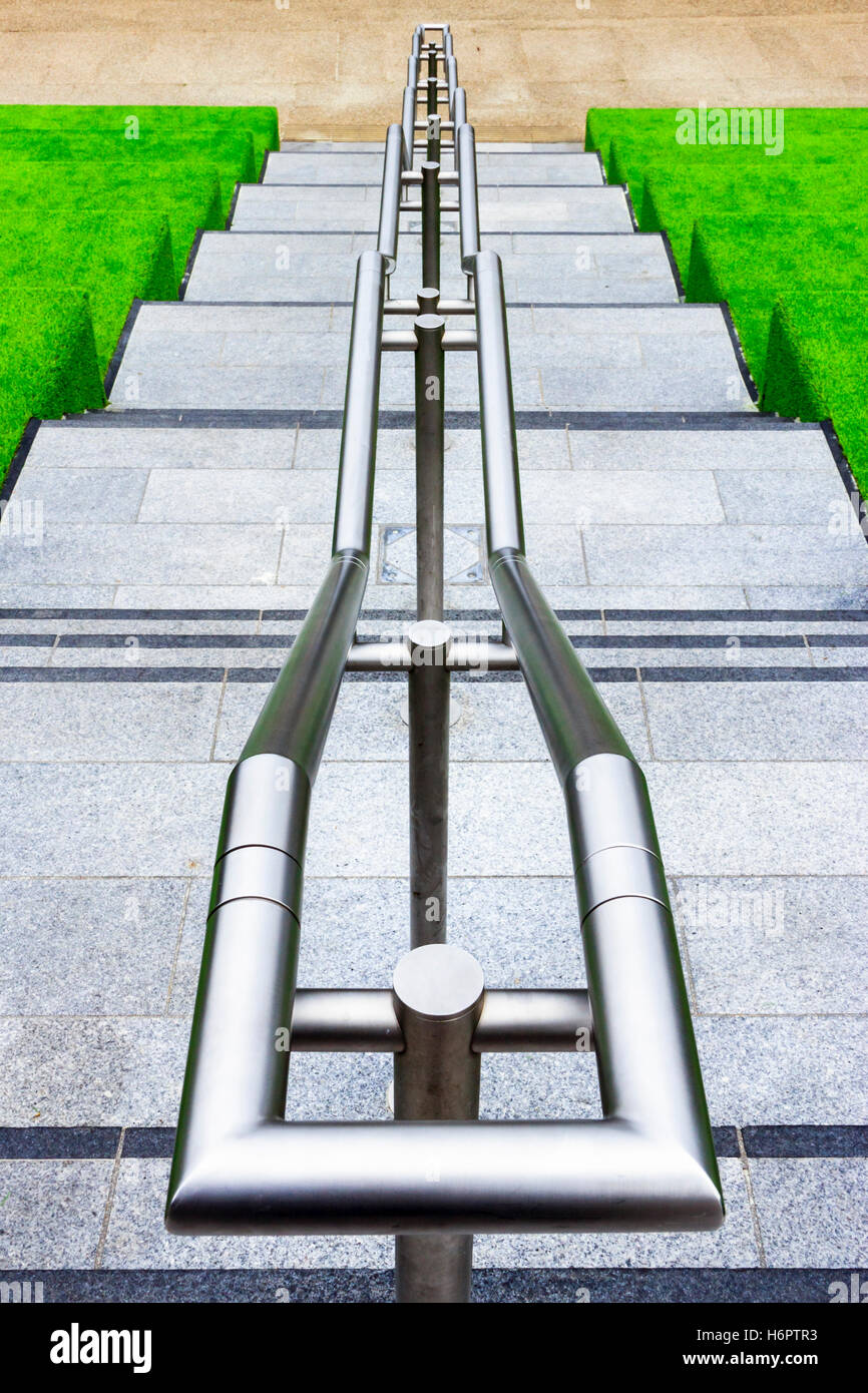 Shiny metal handrail on steps down from Granary Square to Regent's Canal, King's Cross, London, UK Stock Photo