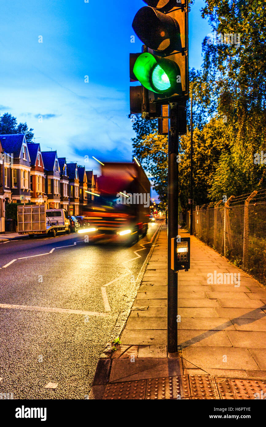 Blue and orange urban night scene with a motion-blurred lorry approaching a green traffic light in the foreground, Archway Road, London, UK Stock Photo