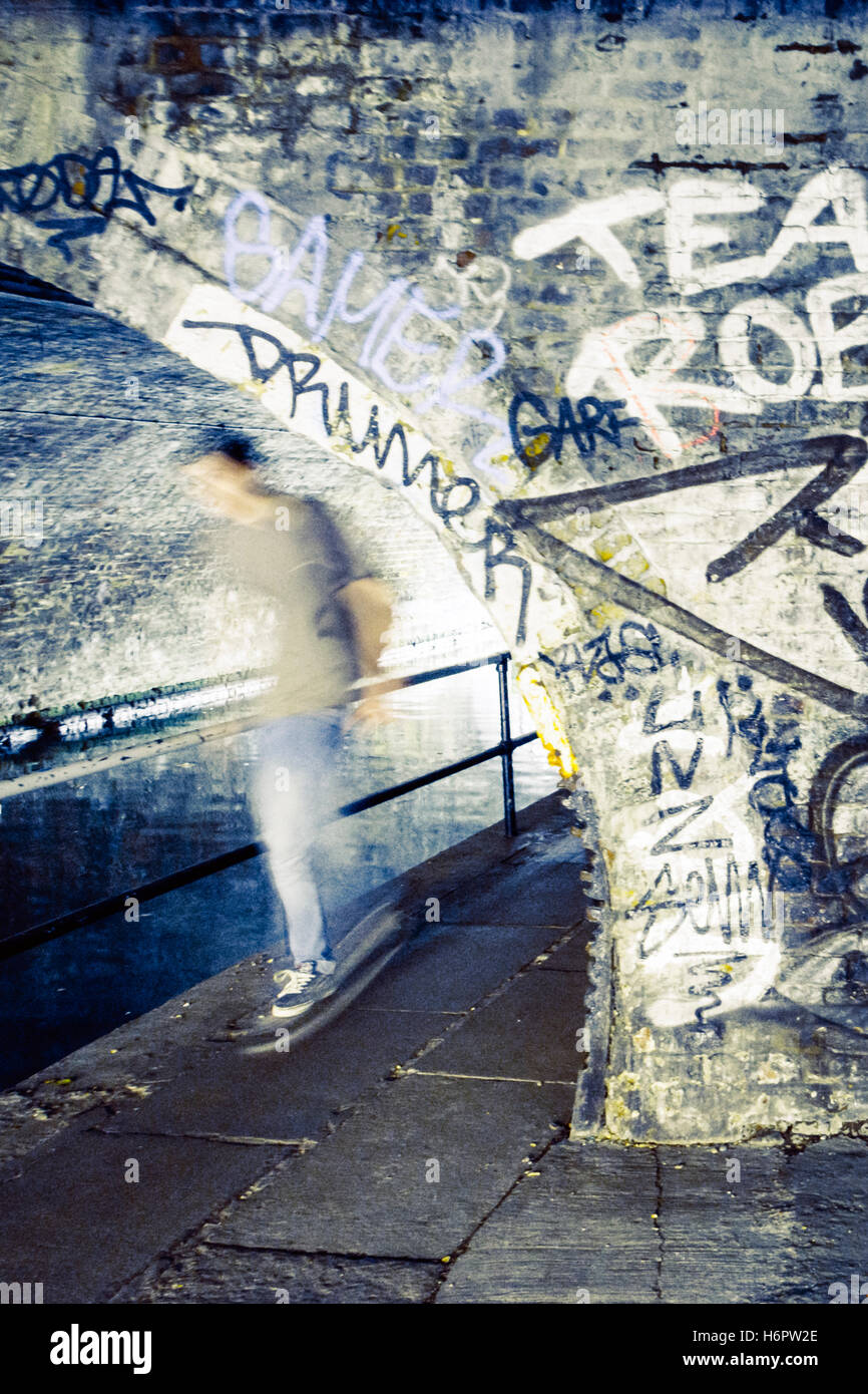 A skateboarder emerging from underneath a bridge over the towpath of Regent's Canal, St. Pancras, London, UK Stock Photo