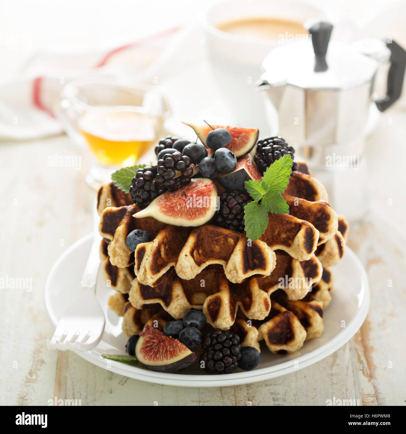 Fluffy breakfast waffles with fresh fruits - Stock Image