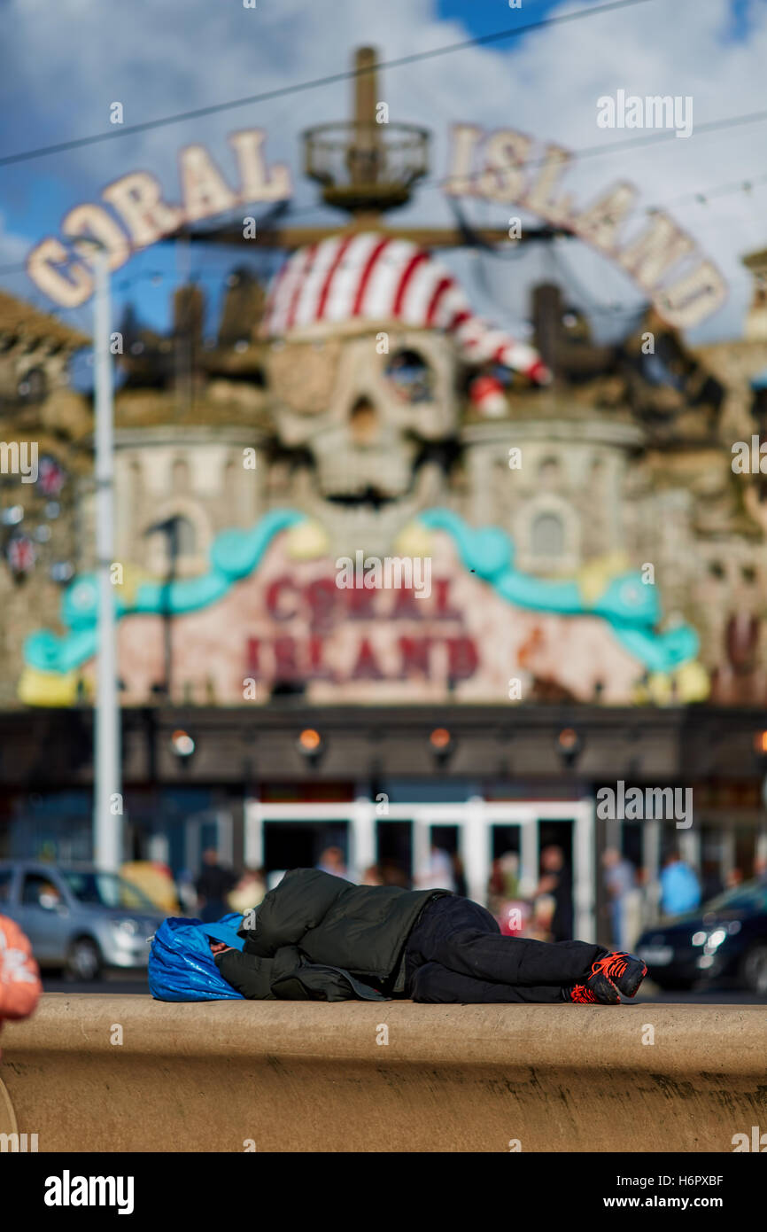 Blackpool sleeping tramp homeless   Holiday sea side town resort Lancashire tourist attractions person with belongings - Stock Image