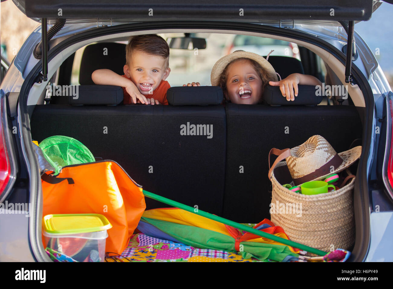 excited kids in car arriving at summer vacation - Stock Image