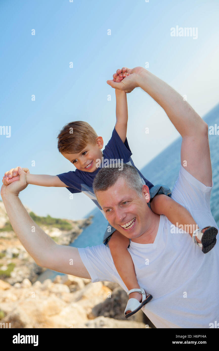 father and son piggyback on summer holiday vacation - Stock Image