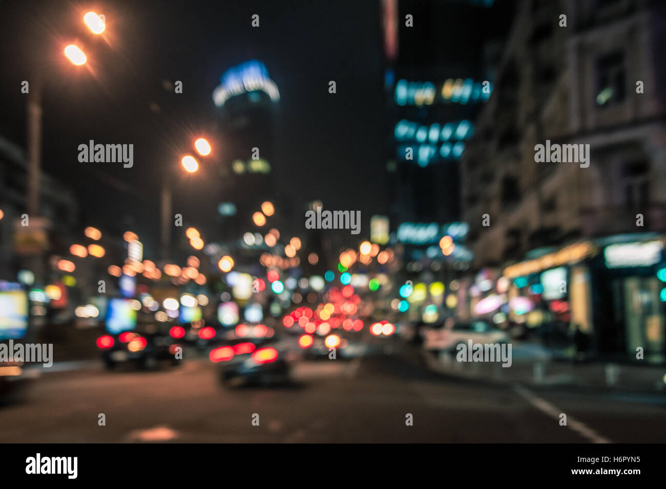 Blurred glowing skyscrapers and cars. Night city street  lights background - Stock Image