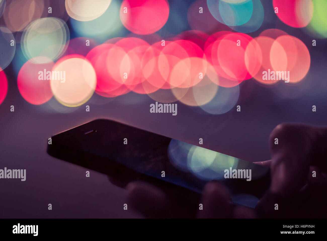 Smart phone in male hands in front of blurred city lights bokeh. Man typing on cell phone at night - Stock Image