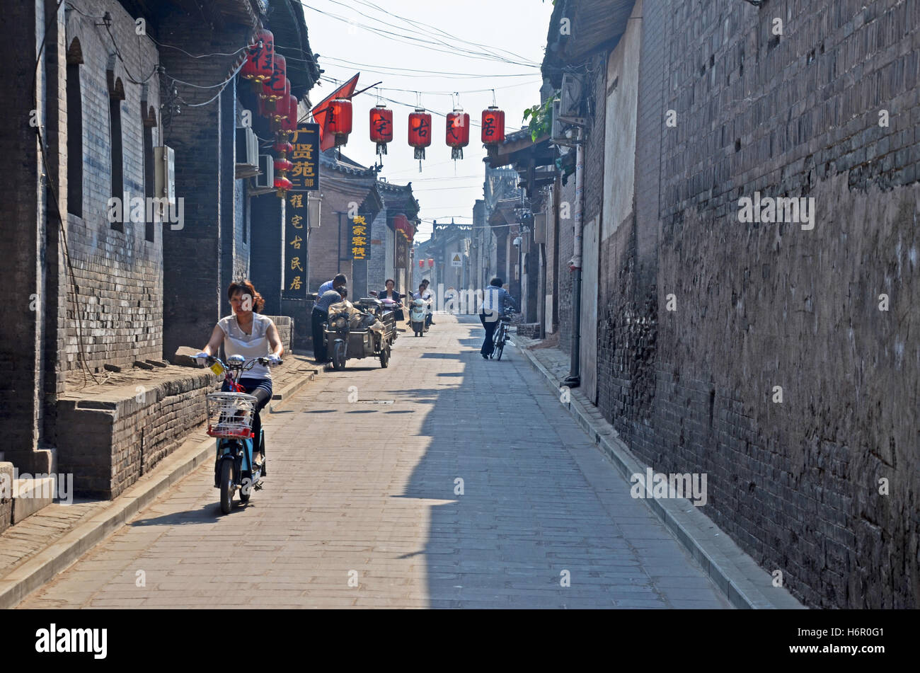 A woman rides a bicycle down a quiet street in Pingyao, Shanxi, China - Stock Image