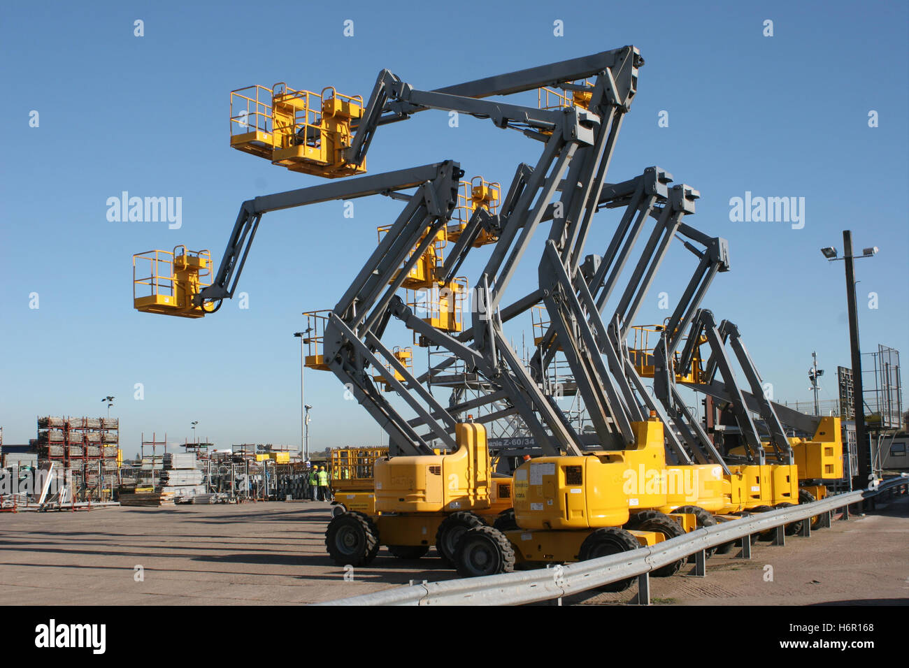 A row of 9 mobile elevating work platforms in a yard with their booms elevated in a range of positions - Stock Image
