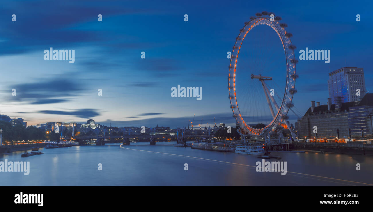 The iconic London Eye ferris wheel on a blue summer's evening lighting up the river and overseeing the boats. - Stock Image