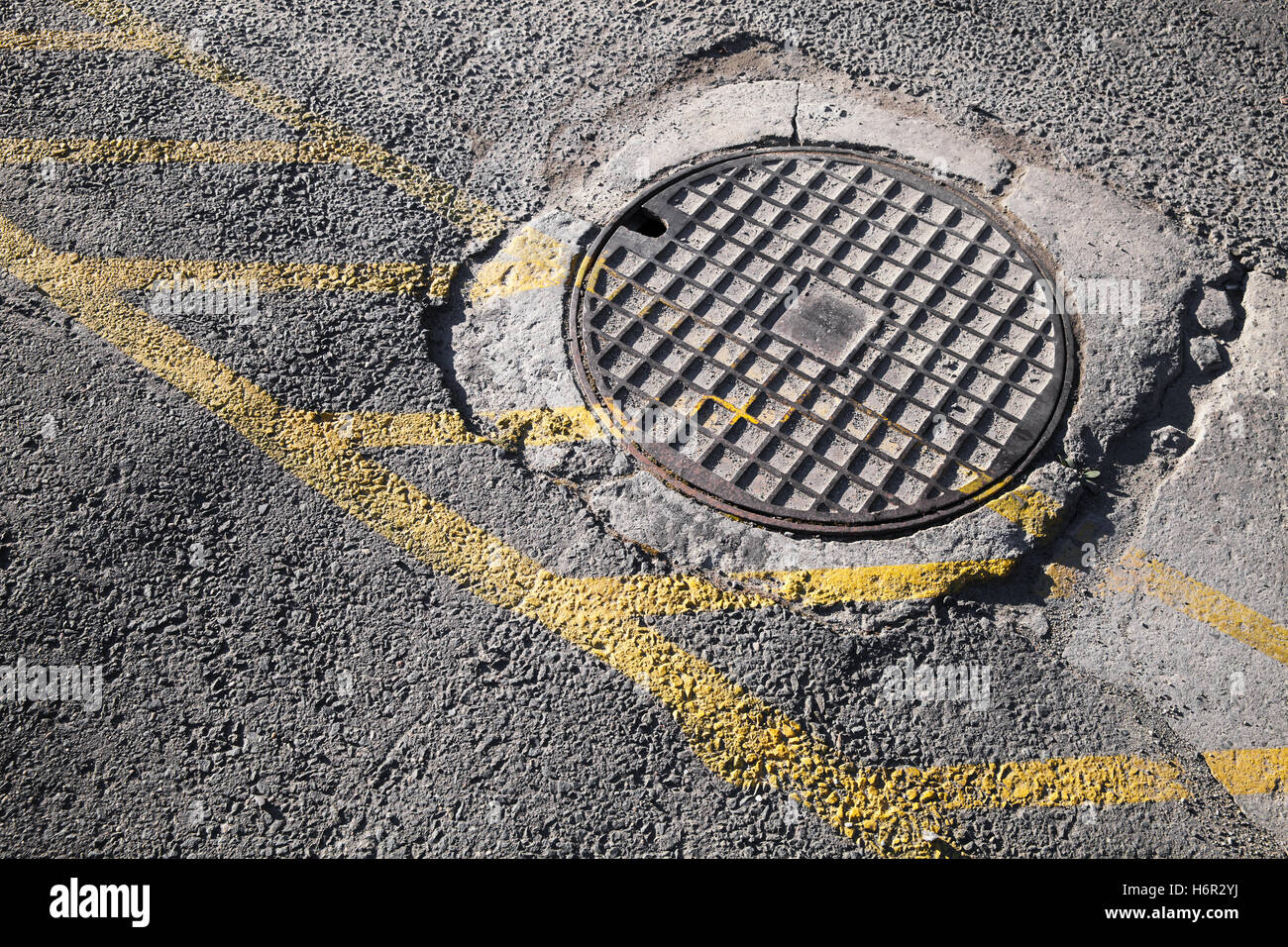 Round hatch in urban pavement, sewer manhole cover with ...