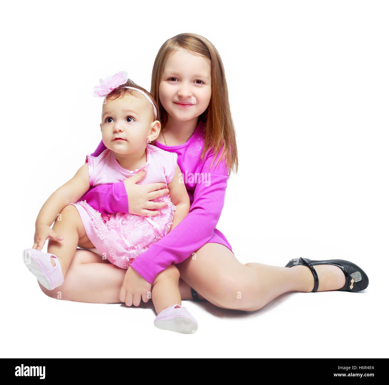two sisters hugging, isolated against white background - Stock Image