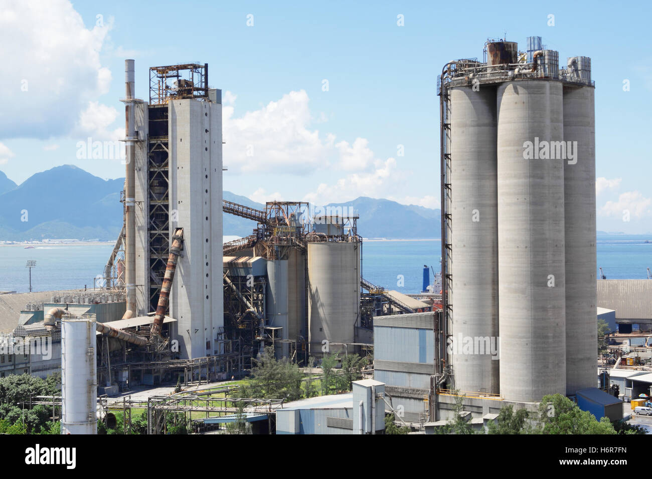 buildings industry concrete work factory cement plant heavy hard construction blue tower stone industry industrial Stock Photo