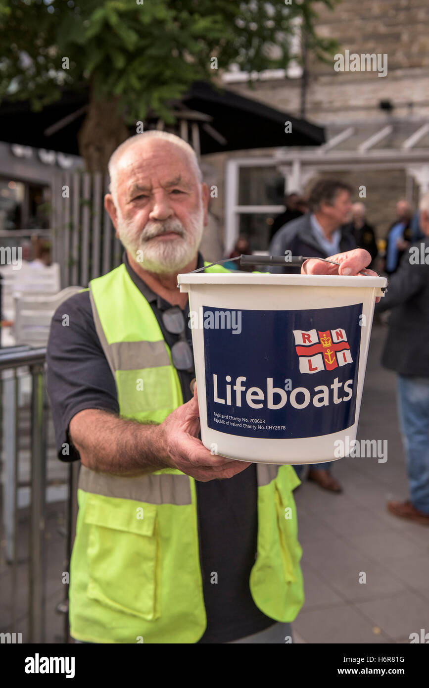 A volunteer charity collector collecting funds for the RNLI. - Stock Image