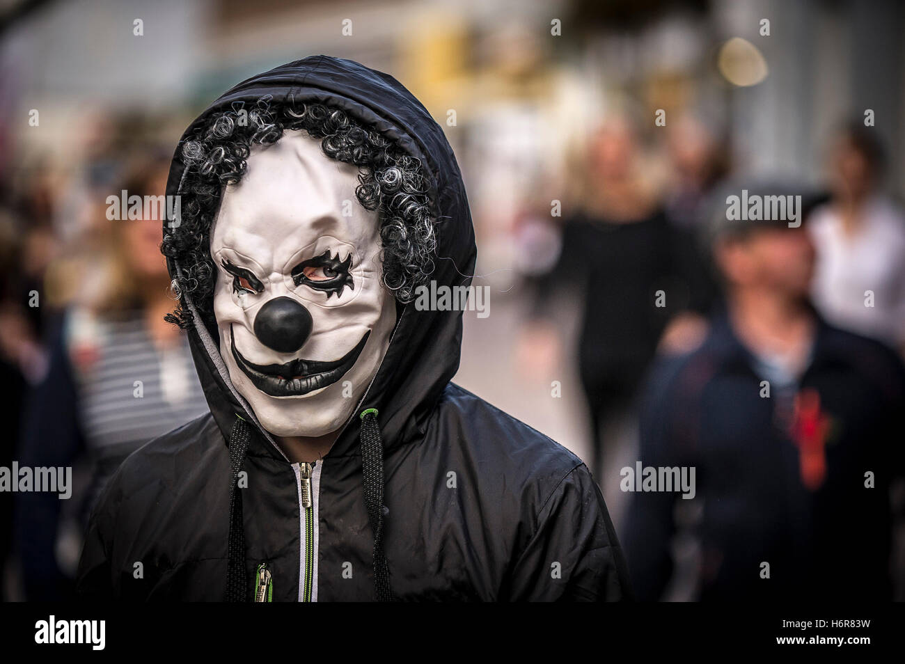 A teenager wearing a clown mask during Halloween celebrations. - Stock Image