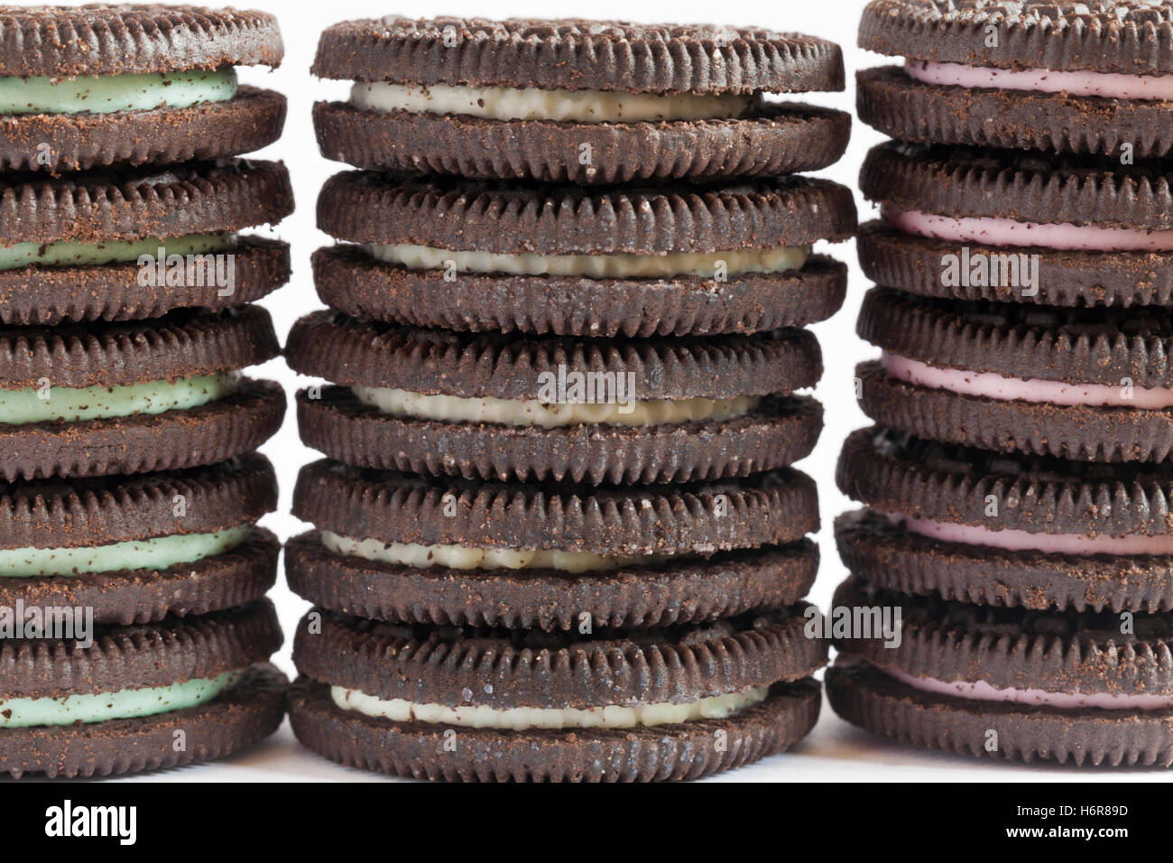 Stack of Mint flavour, Original flavour and Strawberry Cheesecake flavour Oreo biscuits set on white background - Stock Image