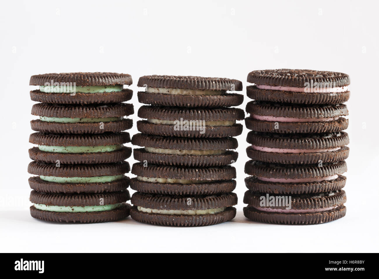 Stack of Mint flavour, Original flavour and Strawberry Cheesecake flavour Oreo biscuits isolated on white background - Stock Image