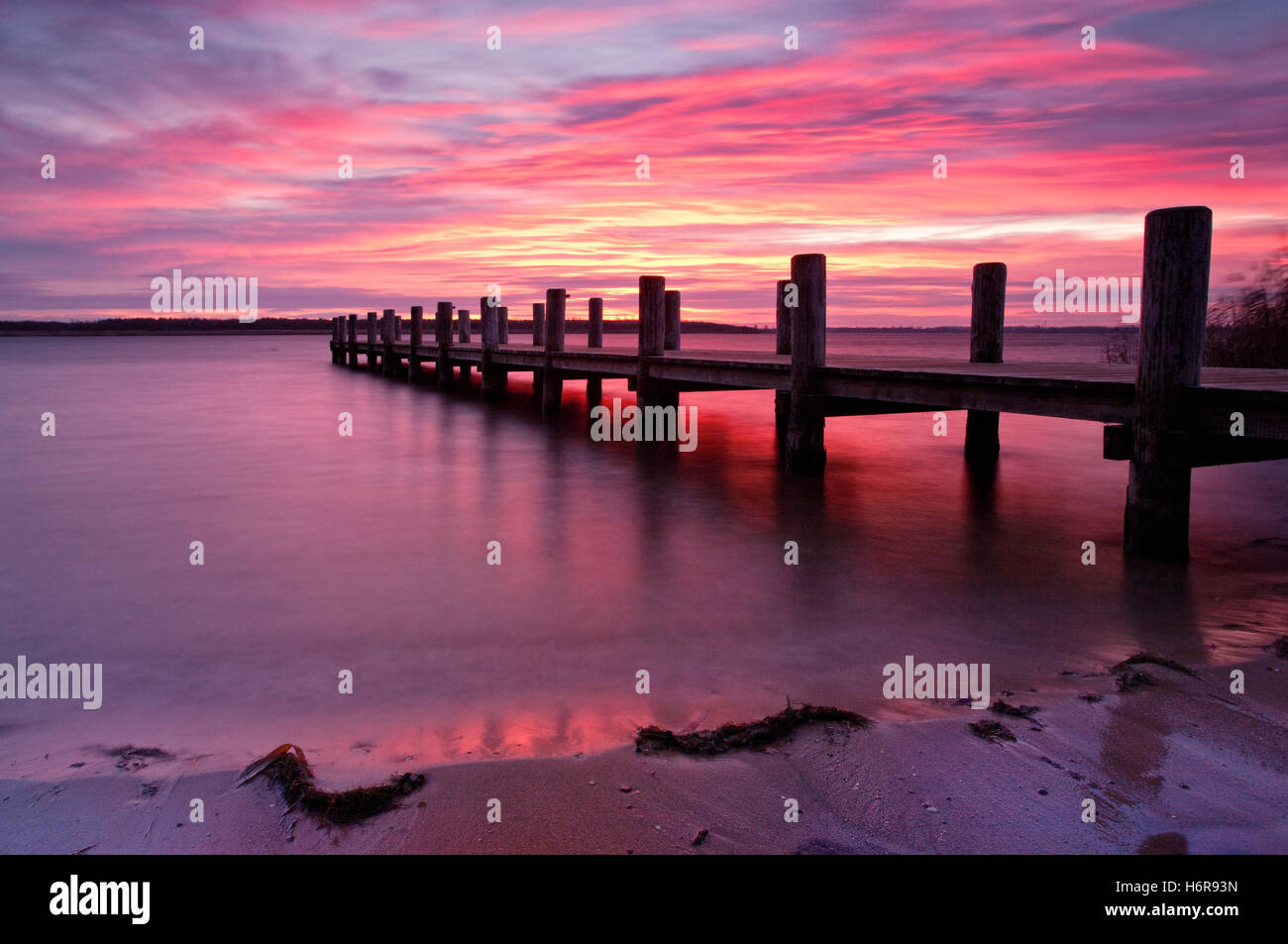 sunrise bridge poeaurora fresh water lake inland water water bank red shore shine shines bright lucent light serene - Stock Image