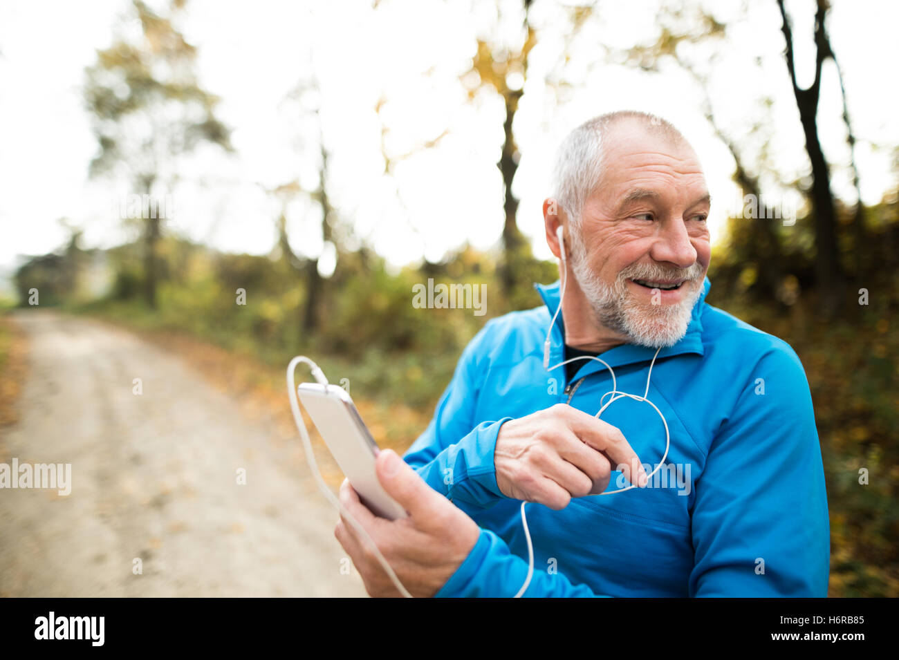 Senior runner in nature with smart phone with earphones. Stock Photo